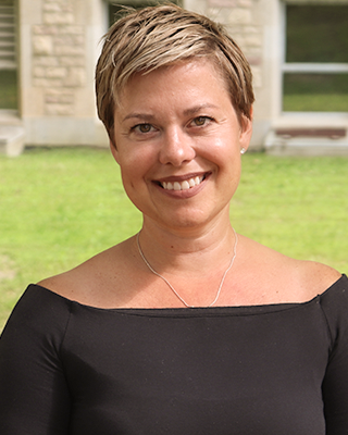 Image of woman with short blonde hair and wide neck black shirt smiling at the camera